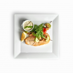 Стейк лосося з овочами доповнений соусом тартар